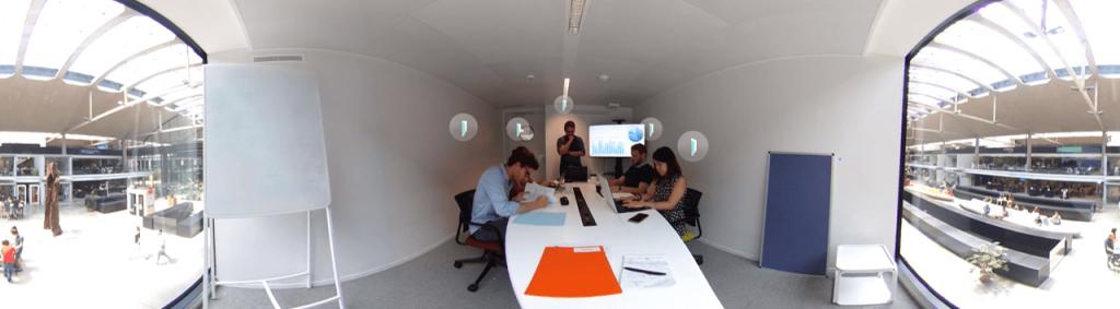Salle de réunion avec 5 personnes qui travaillent